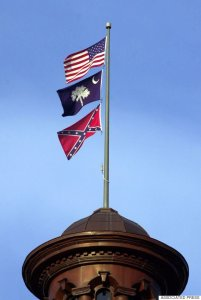 The Confederate flag flies on the dome of the Statehouse in Columbia, S.C., Friday, June 30, 2000. The flag will come down from the dome during a ceremony Saturday along with Confederate flags that fly in the House and Senate chambers. (AP Photo/Eric Draper)