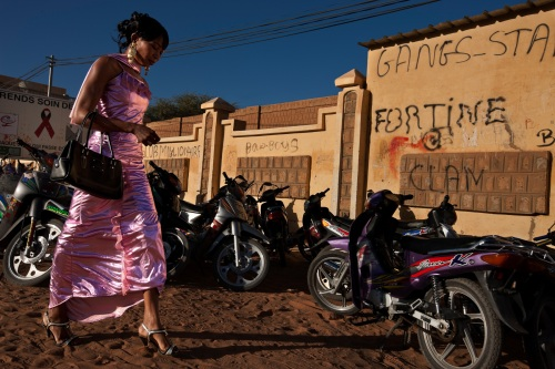 TIMBUKTU, MALI, JANUARY 2010: A young women wearing a sophisticated dress strides into the local high school on the main street of Timbuktu, Mali, January 6 2010. Timbuktu is a fundamentally conservative city of Mosques and high school is one of the very few arenas for kids to show their less conservative side. High School in Timbuktu is similar to high school in many western cities, an opportunity for kids to strut their stuff. In Timbuktu that manifests in a modern dress sense with a surprisingly sophisticated edge for most of the kids. (Photo by Brent Stirton/National Geographic.)